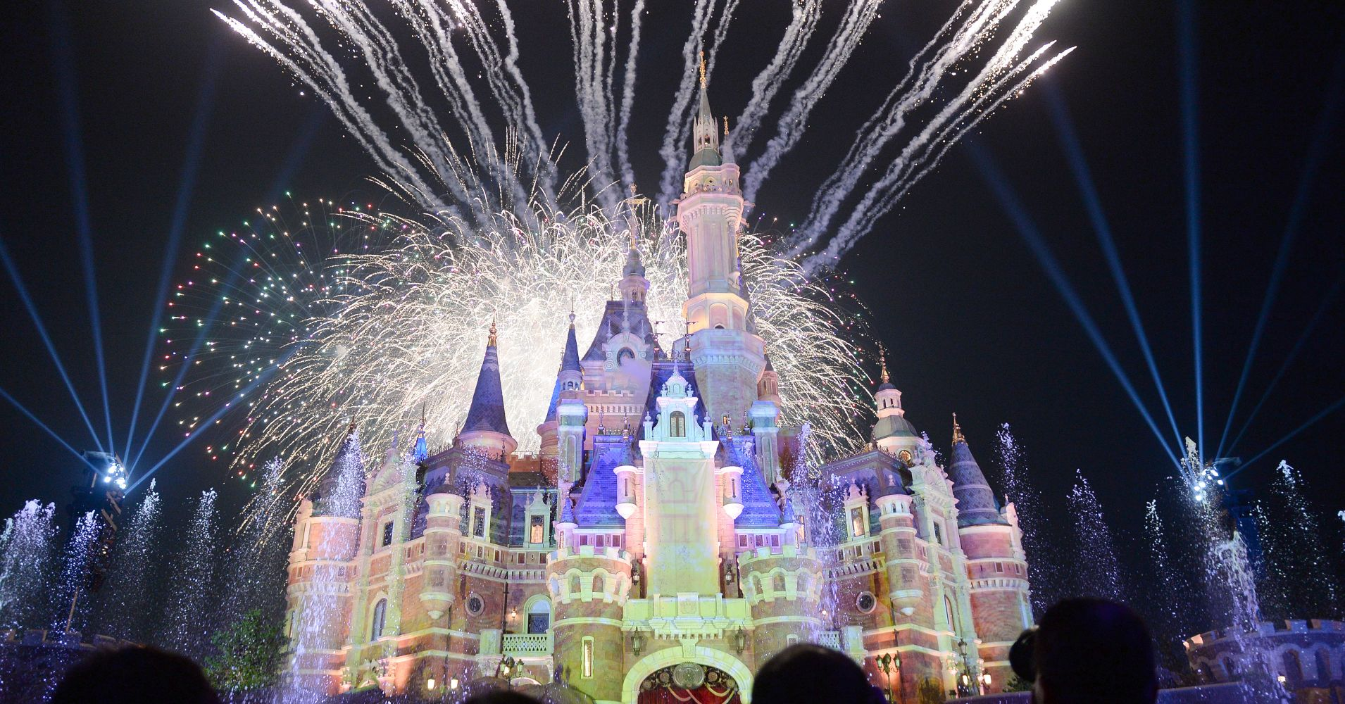 Tourists watch the celebration show marking the first anniversary of the Shanghai Disney Resort at the 196.8-foot Enchanted Storybook Castle on June 16, 2017 in Shanghai, China.