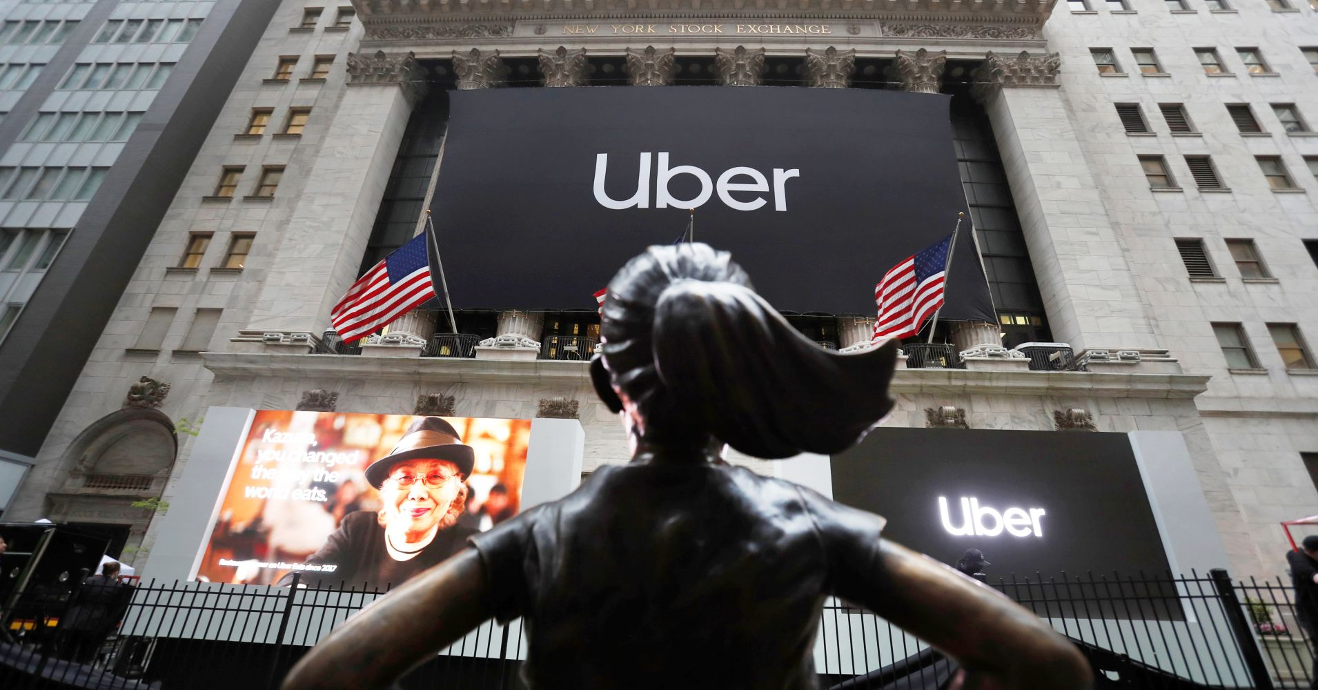 The Fearless Girl statue is seen in the foreground as a banner announcing the IPO of Uber Technologies hangs outside the New York Stock Exchange, May 10, 2019.